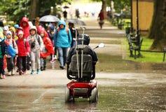 Um homem idoso em uma cadeira de rodas mecânica está passando pelo alee do parque após um grupo de passagem de crianças Simpatia  imagens de stock