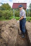 Um homem idoso está escavando a terra para construir uma cama profunda de Fotos de Stock