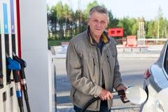 Um homem idoso está no posto de gasolina com o bocal de abastecimento nas mãos Fotografia de Stock