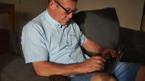 Um homem idoso paga contas da casa usando o Internet e um portátil Operação bancária em linha, Internet banking video estoque