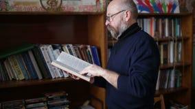 Um homem idoso relaxa na aposentadoria, livros de leitura em sua biblioteca vídeos de arquivo