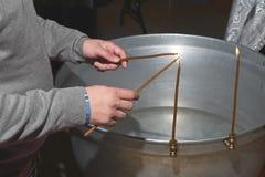 Um homem ilumina velas antes do batismo de uma criança imagens de stock