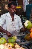 Um homem indiano corta um coco verde novo com um interruptor inversor afiado FO imagens de stock royalty free