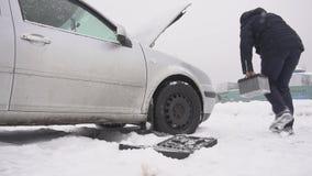Um homem instala uma bateria de carro em um carro, começo frio de um conjunto diesel do automóvel, movimento lento do inverno, ac video estoque