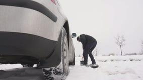 Um homem instala uma bateria de carro em um carro, começo frio de um conjunto diesel do automóvel, movimento lento do inverno, ac filme