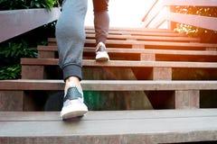 Um homem intensifica ao sucesso, homem do esporte está escalando na etapa de madeira Foto de Stock Royalty Free