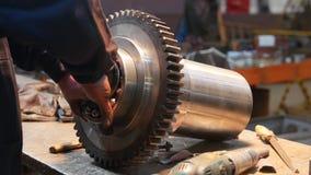 Um homem introduz uma roda de carregamento em uma engrenagem do metal e toma então o moedor - fábrica filme