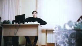 Um homem irritado joga o papel amarrotado longe da tabela video estoque