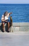 Um homem joga com um cão Imagem de Stock