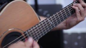 Um homem joga na guitarra acústica video estoque