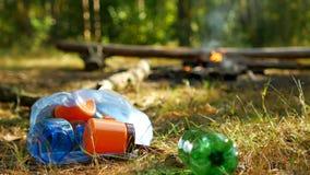 Um homem joga uma garrafa plástica na natureza, queimaduras de um fogo no fundo, a recreação exterior, a natureza e o lixo, acamp filme
