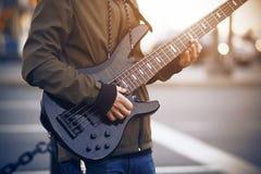 Um homem joga uma guitarra-baixo preta na rua imagens de stock royalty free