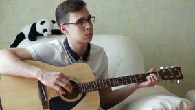 Um homem joga uma guitarra de madeira video estoque