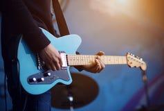 Um homem joga uma guitarra elétrica azul em um fundo azul imagens de stock