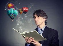 Um homem lê um livro Foto de Stock Royalty Free