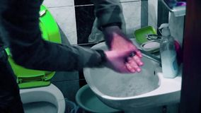Um homem lava suas mãos no banheiro video estoque