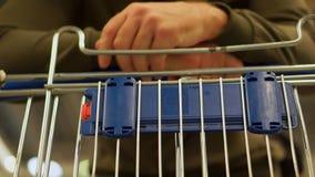 Um homem leva um carro para produtos no supermercado video estoque