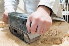 Um homem lustra uma placa de madeira Fotografia de Stock