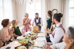 Um homem maduro com amigos e presentes de abertura da família em uma festa de anos imagem de stock