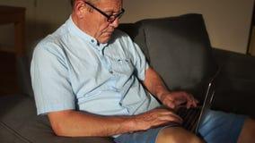 Um homem maduro está trabalhando com um noutbeck que senta-se no sofá Emprego remoto, Internet banking para pensionista video estoque