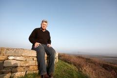 Um homem maduro que senta-se em uma parede Imagem de Stock Royalty Free