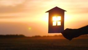 Um homem mantém uma casa do papel em sua mão contra o por do sol e passa-a à mão da mulher O conceito da uni?o vídeos de arquivo
