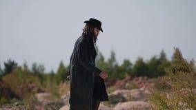 Um homem misterioso em uma capa de chuva anda rapidamente em colis?es secas pequenas no deserto video estoque