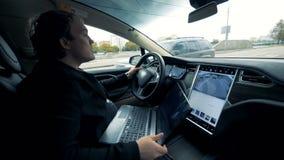 Um homem monta um electromobile na estrada Condução automatizada futurista do auto do carro elétrico vídeos de arquivo