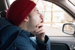 Um homem monta na estrada no inverno, bocejos de um homem na roda, cansado da condução imagens de stock royalty free