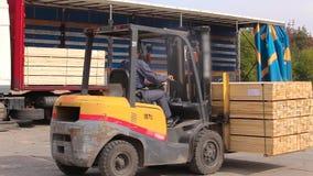 Um homem monta uma empilhadeira com madeira video estoque
