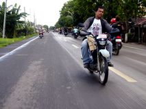 Um homem monta uma motocicleta em uma estrada principal na província de Samar, Leyte, Filipinas Imagens de Stock Royalty Free