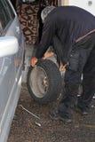 Um homem montou em seus pneus do inverno do carro Fotos de Stock Royalty Free
