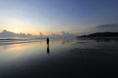 Um homem mostrado em silhueta em uma praia Foto de Stock Royalty Free