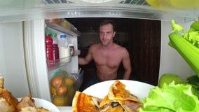 Um homem muscular novo abre o refrigerador na noite Fome da noite Dieta glutonaria foto de stock