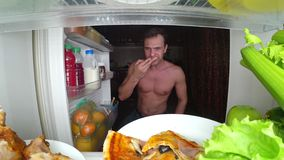 Um homem muscular novo abre o refrigerador na noite Fome da noite Dieta glutonaria imagem de stock royalty free