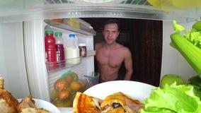 Um homem muscular novo abre o refrigerador na noite Fome da noite Dieta glutonaria fotografia de stock