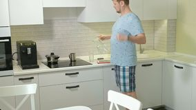 Um homem na água potável dos pijamas na cozinha Manhã filme