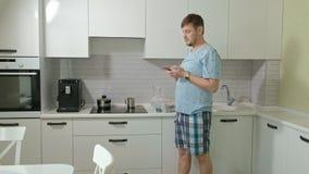 Um homem na água potável dos pijamas na cozinha Manhã video estoque