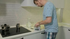 Um homem na água potável dos pijamas na cozinha Manhã vídeos de arquivo