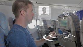 Um homem na cabine com um dispositivo esperto, seleciona opções confortáveis de um voo HUD O conceito de artificial