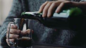 Um homem na camiseta que derrama a cerveja de cerveja pilsen na caneca de cerveja, bebe-a toda satisfeito com o resultado Estilo  vídeos de arquivo