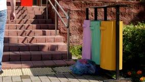 Um homem na cidade joga um saco do lixo após a lata de lixo, close-up video estoque