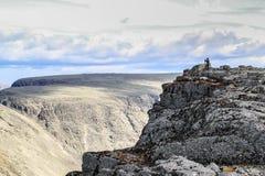 Um homem na distância faz uma foto das montanhas entre a rocha de Khibiny em Carélia, Rússia imagem de stock royalty free