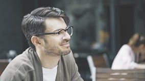 Um homem na escuta de sorriso dos monóculos no café fora Imagem de Stock