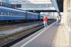 Um homem na estação está esperando o trem indivíduo em uma camiseta vermelha em uma plataforma railway blurry foto de stock