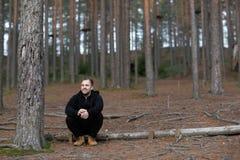 Um homem na floresta está sentando-se felicidade foto de stock