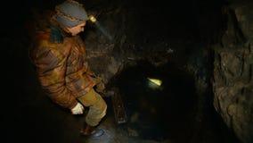 Um homem na obscuridade com uma lanterna elétrica em uma mina abandonada encontra apoios de madeira video estoque