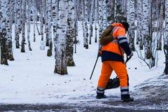 Um homem na roupa de funcionamento com uma pá remove a neve na trilha no parque no inverno Foto de Stock Royalty Free