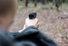 Um homem na roupa militar est? apontando com uma pistola imagem de stock