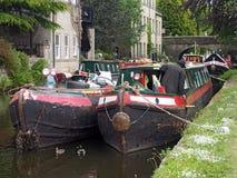 um homem nas barcas velhas nos barcos estreitos o recolhimento do clube que guardado no pode feriado oficial no canal do rochdale fotos de stock